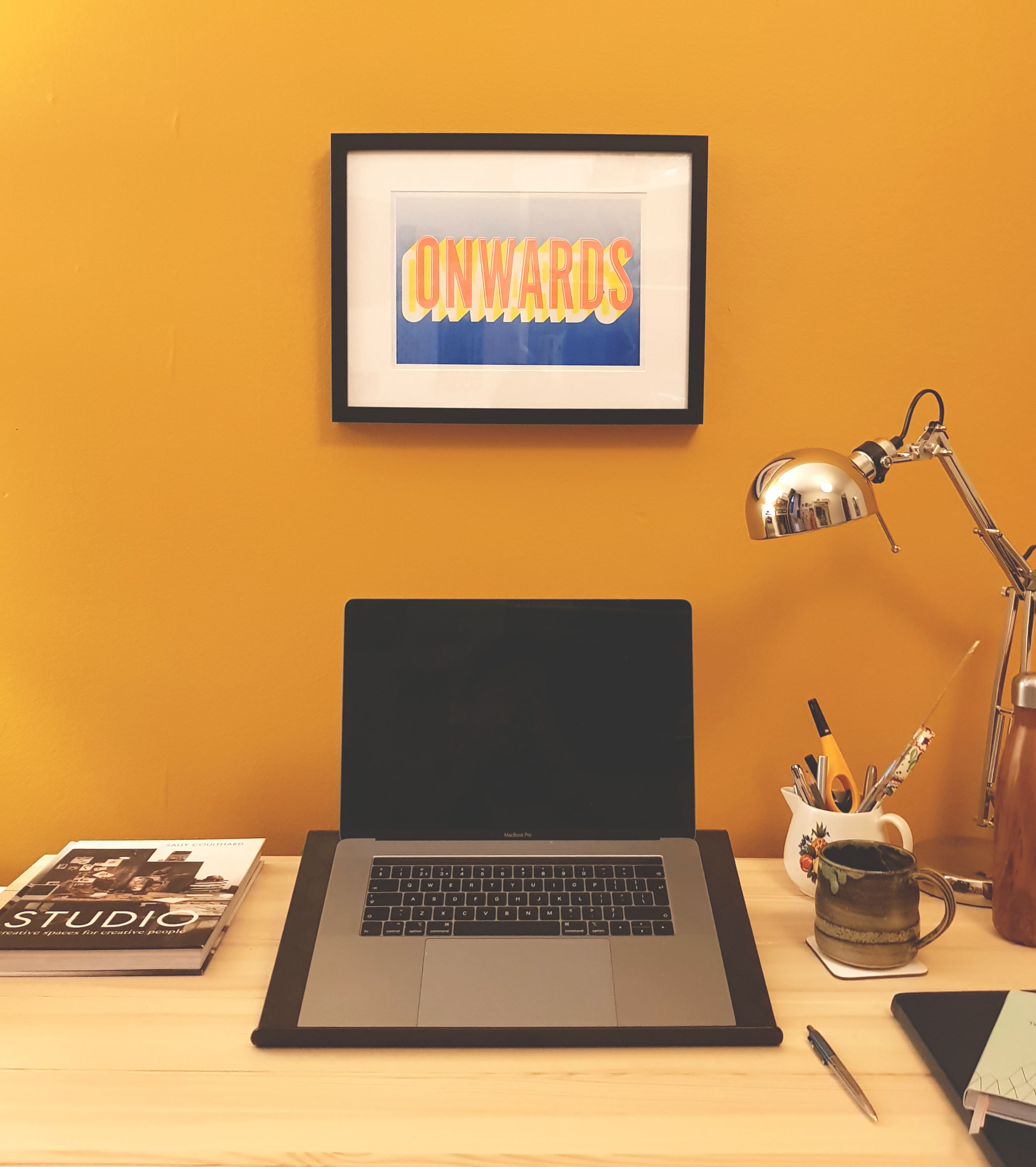 Desk with computer and motivational poster