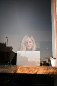Katie Partridge seen through a window at her laptop