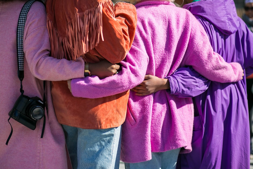 A group of people with colourful jackets have their arm around each other